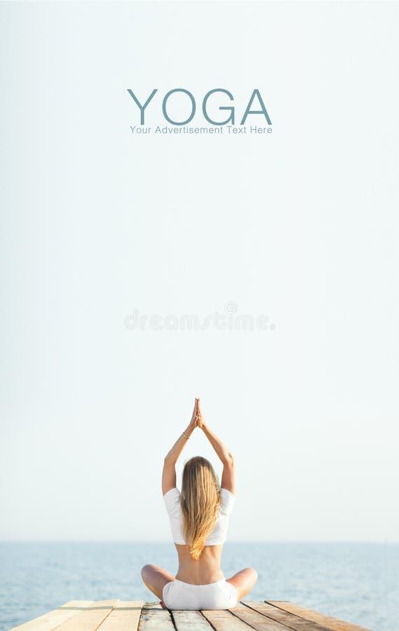 Yoga di pratica della bella donna bionda alla spiaggia immagine stock
