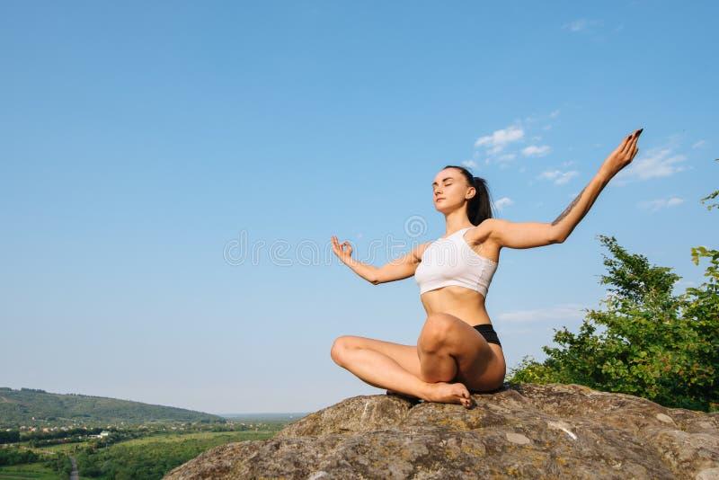 Yoga di pratica della bella forte donna castana sull'orlo della scogliera e del rilassamento immagini stock