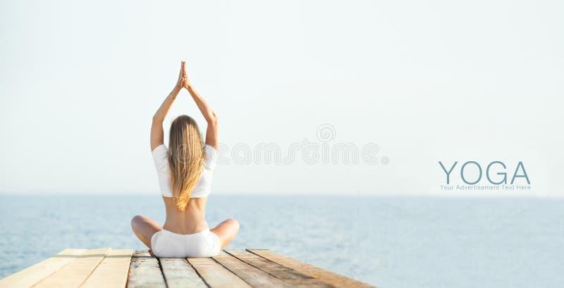 Yoga di pratica della bella ragazza del positiveblond a fotografia stock