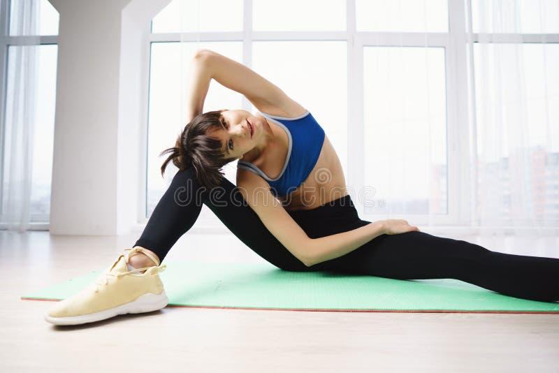 Yoga di pratica della donna adatta in studio immagini stock