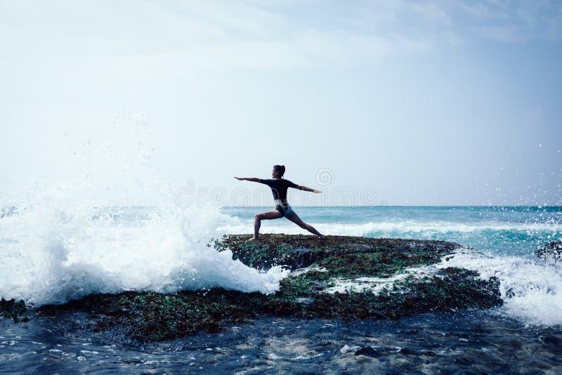 Yoga di pratica della donna al bordo di corallo della scogliera della spiaggia immagini stock