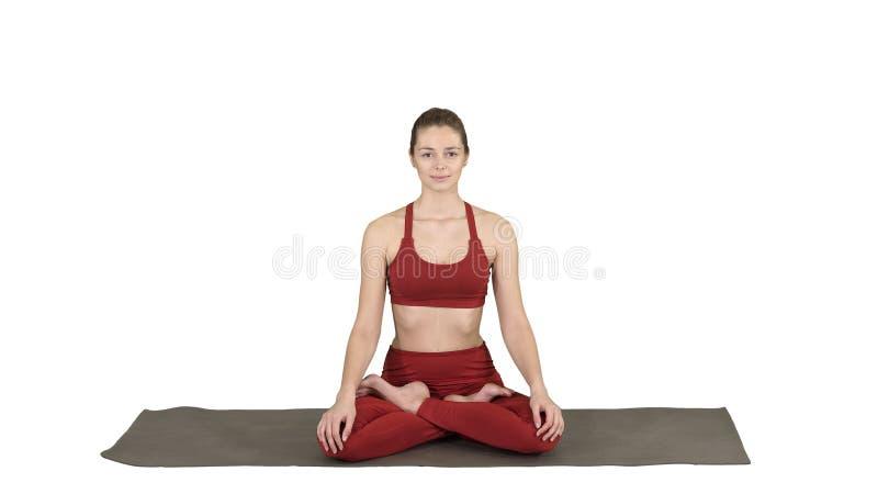 Yoga di pratica della donna attraente sportiva, sedentesi nell'esercizio di Lotus, posa di Siddhasana che respira sul fondo bianc immagine stock