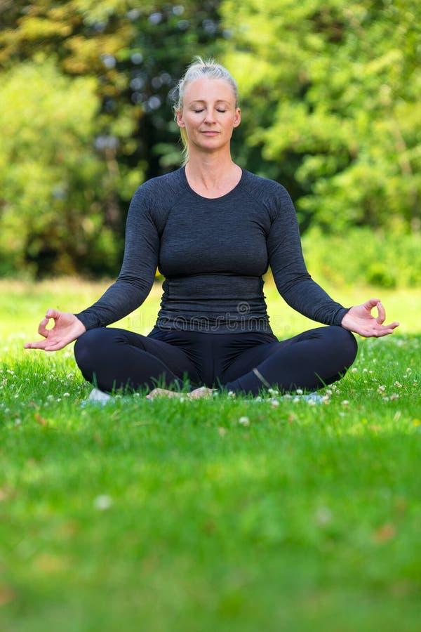 Yoga di pratica della donna in buona salute adatta Medio Evo maturo fuori immagini stock
