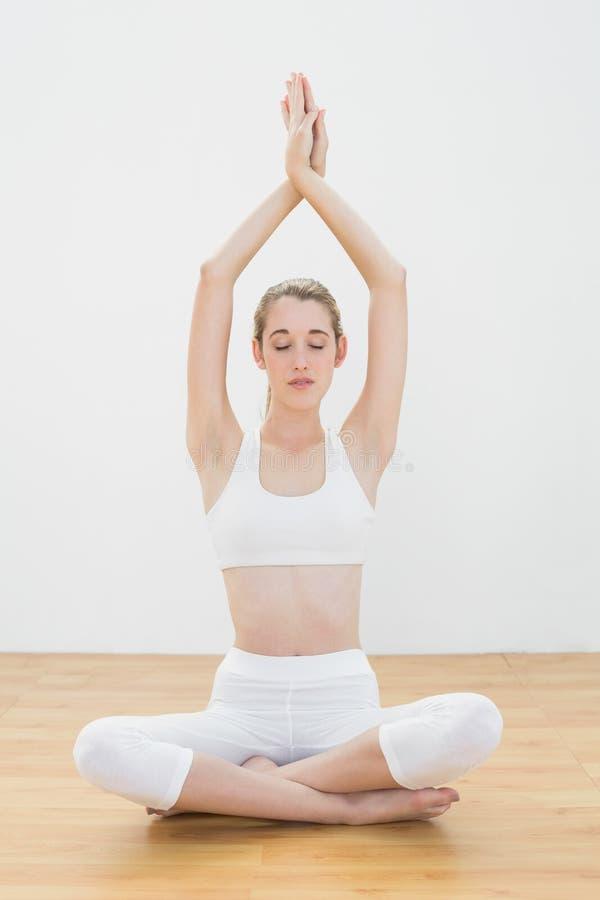 Yoga di pratica della donna calma attraente che si siede nella posizione di loto nella palestra immagine stock libera da diritti