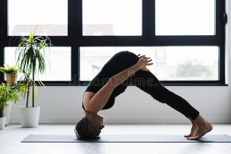 Yoga di pratica della donna caucasica matura sul pavimento del salone fotografie stock libere da diritti