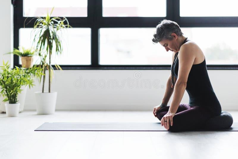 Yoga di pratica della donna caucasica matura sul pavimento del salone immagine stock libera da diritti