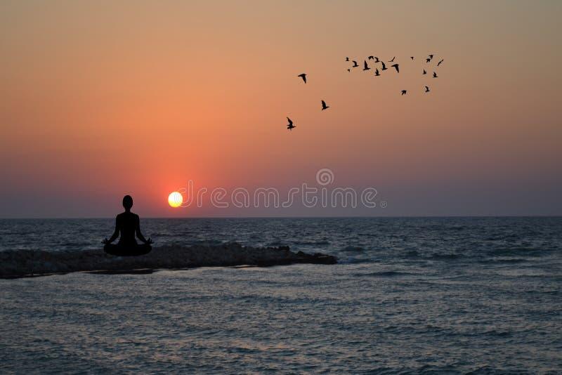 Yoga di pratica della donna e meditare su alba fotografia stock