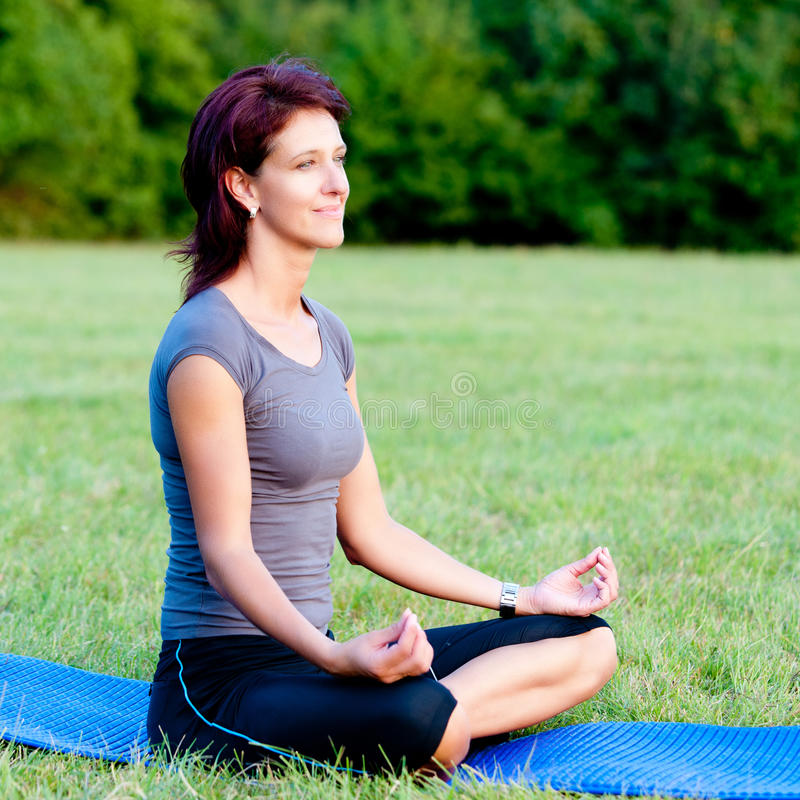 Yoga di pratica della donna esterna in sosta immagine stock libera da diritti