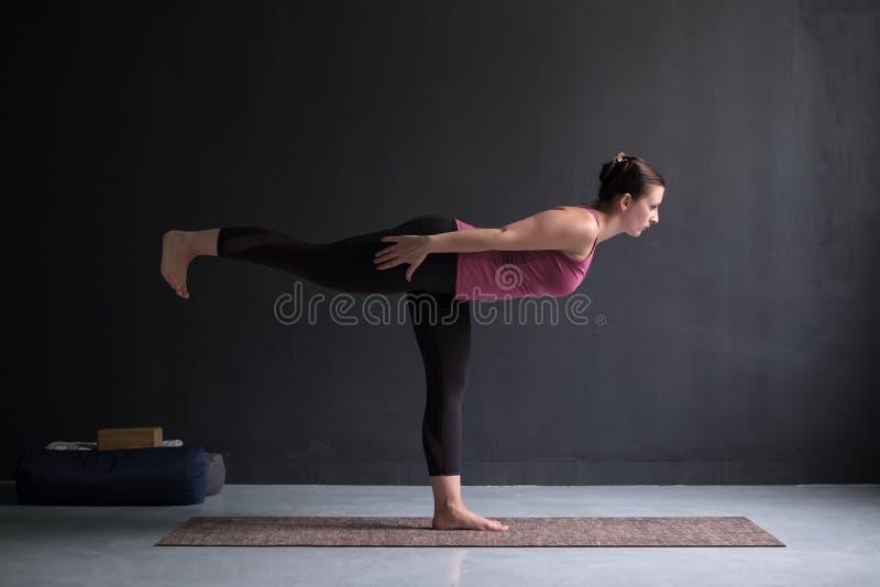 Yoga di pratica della donna, facente esercizio del guerriero III, posa di Virabhadrasana 3 immagini stock