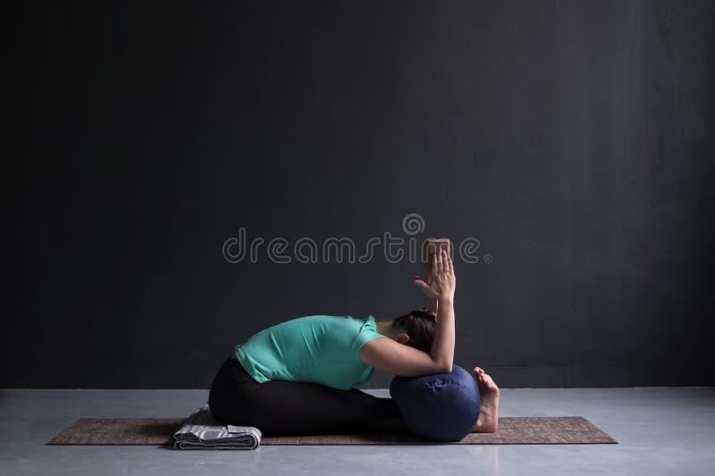 Yoga di pratica della donna, posa di andata messa della curvatura, facendo uso del blocco e del sostegno fotografia stock