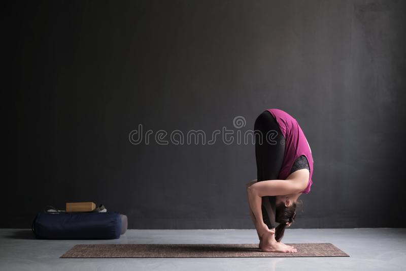 Yoga di pratica della donna sportiva, esercizio di andata stante della curvatura, posa di uttanasana fotografia stock
