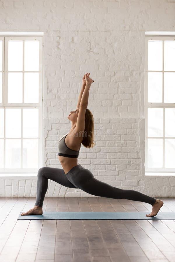 Yoga di pratica della donna, stante nella posa di anjaneyasana, cavaliere del cavallo, verticale fotografie stock