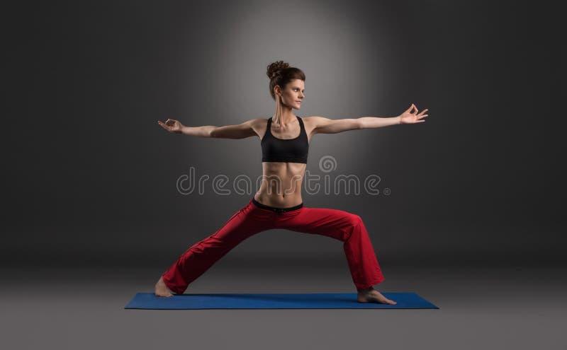 Yoga di pratica della donna in studio, sul contesto grigio fotografie stock