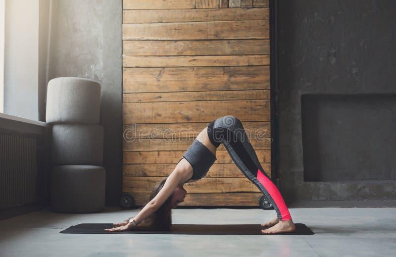 Yoga di pratica della giovane donna attraente fotografia stock