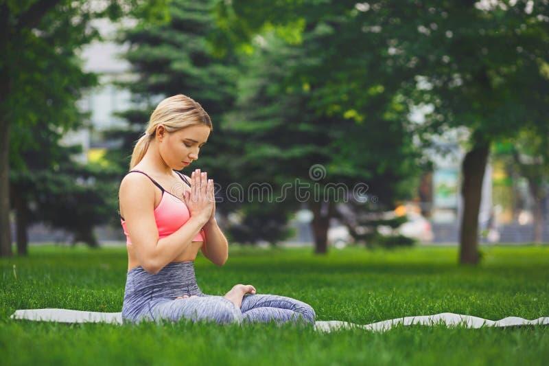 Yoga di pratica della giovane donna attraente che si siede nel padmasana immagini stock libere da diritti