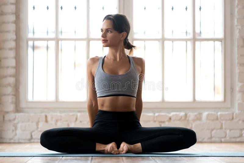 Yoga di pratica della giovane donna attraente sportiva, facente farfalla e fotografie stock