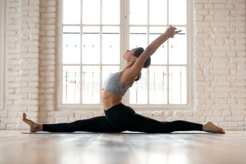 Yoga di pratica della giovane donna attraente sportiva, facente Hanumanasan immagine stock