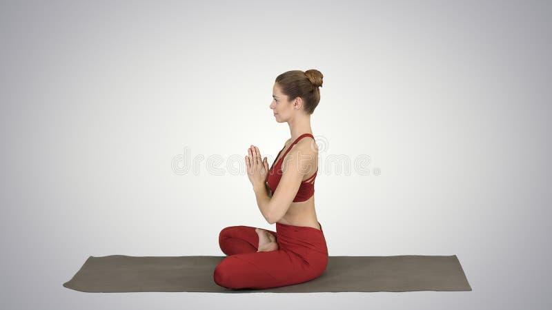 Yoga di pratica della giovane donna attraente sportiva, facente posa di Lotus sul fondo di pendenza fotografia stock