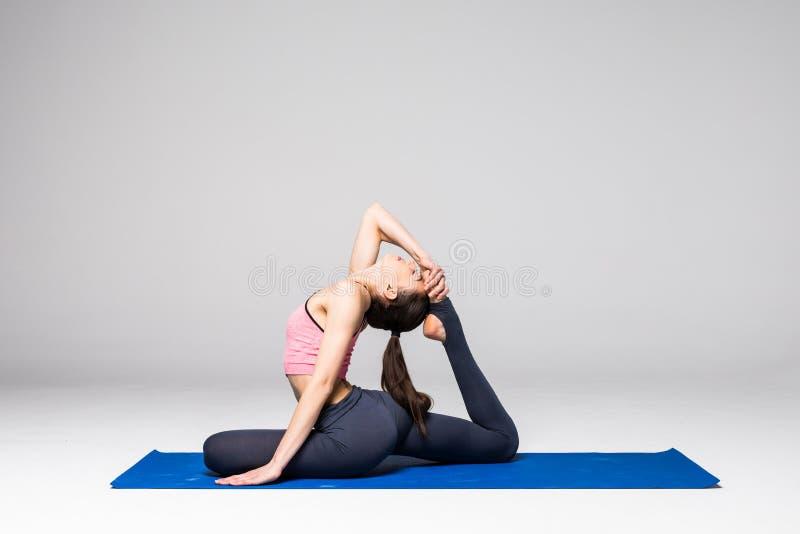 Yoga di pratica della giovane donna attraente, stando nell'esercizio differente di yoga, abiti sportivi d'uso isolati su fondo gr fotografia stock libera da diritti