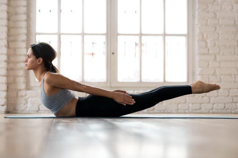 Yoga di pratica della giovane donna sportiva, facente il doppio exerc di scosse della gamba fotografia stock