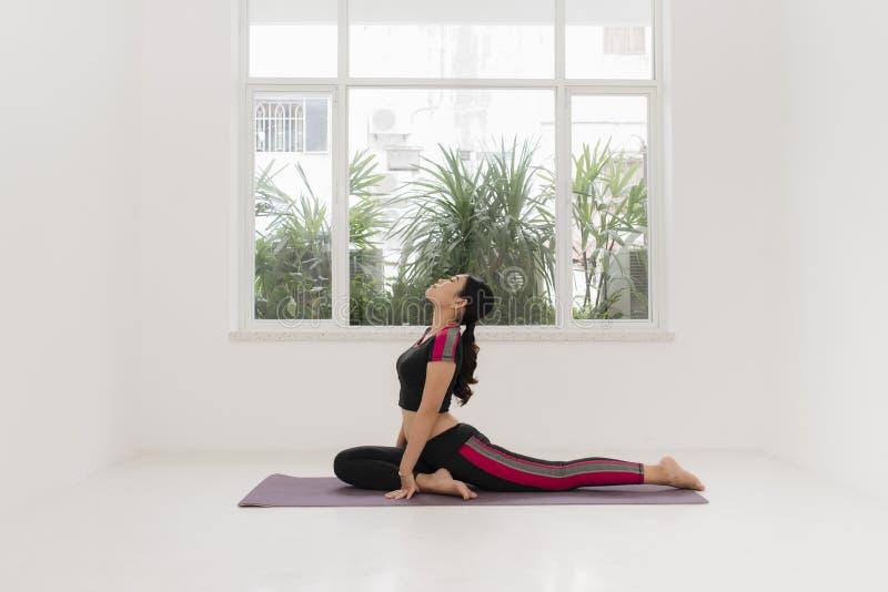 Yoga di pratica della giovane donna sportiva vicino alla finestra fotografia stock
