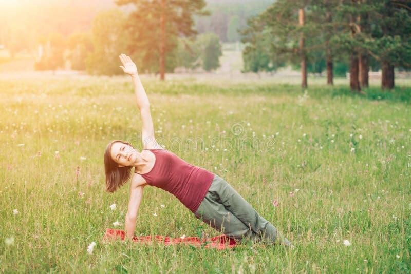 Yoga di pratica della giovane donna sui precedenti dei campi e delle foreste di estate Salute, sport, felicità fotografia stock