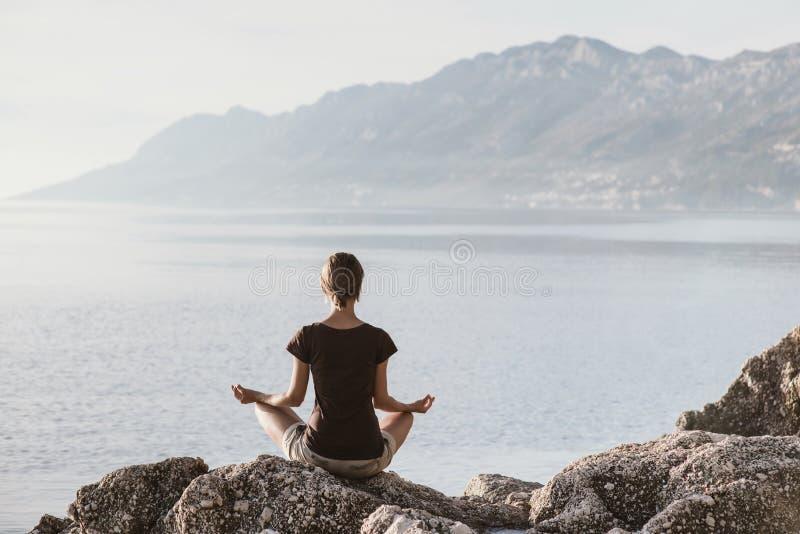 Yoga di pratica della giovane donna vicino al mare Concetto di meditazione e di armonia immagini stock