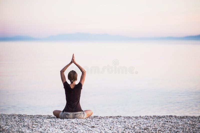Yoga di pratica della giovane donna vicino al mare Concetto di meditazione e di armonia immagine stock