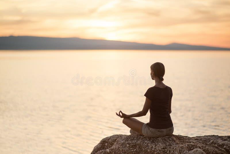 Yoga di pratica della giovane donna vicino al mare al tramonto Armonia, meditazione e concetto di viaggio Stile di vita sano fotografie stock libere da diritti