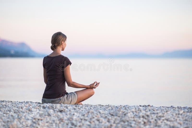 Yoga di pratica della giovane donna vicino al mare al tramonto Armonia, meditazione e concetto di viaggio Stile di vita sano immagine stock libera da diritti