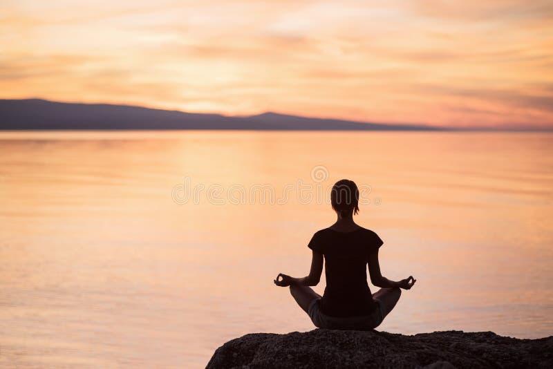 Yoga di pratica della giovane donna vicino al mare al tramonto Armonia, meditazione e concetto di viaggio Stile di vita sano immagini stock