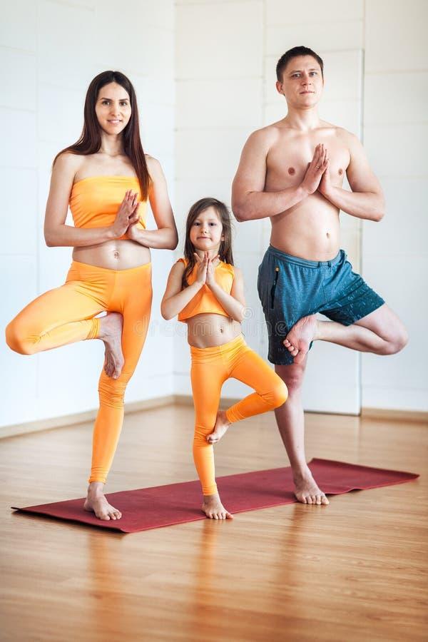Yoga di pratica della giovane famiglia attraente, facendo gesto del namaste, risolvendo, abiti sportivi d'uso, vestito arancio immagine stock libera da diritti