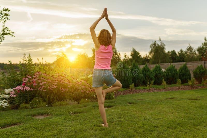 Yoga di pratica della ragazza, meditante su fondo di tramonto di estate, su erba verde, prato inglese vicino alla casa fotografia stock libera da diritti