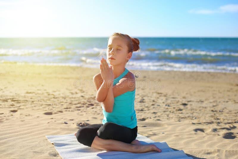 Yoga di pratica della ragazza sulla spiaggia fotografie stock