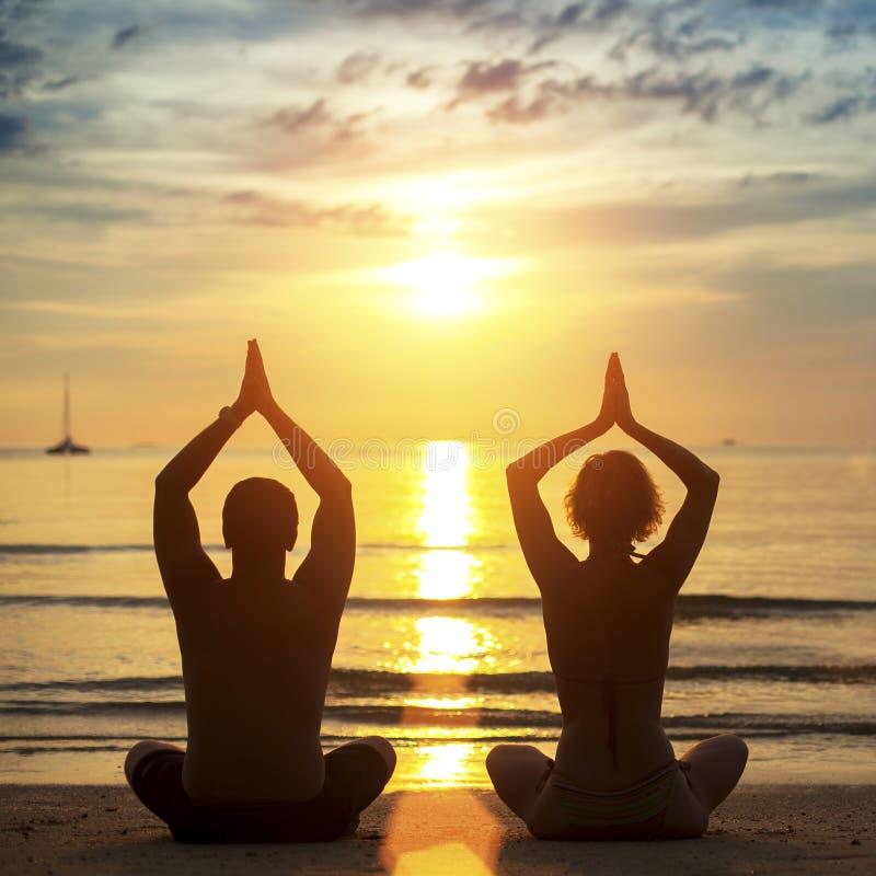 Yoga di pratica delle giovani coppie sulla spiaggia durante il tramonto immagine stock