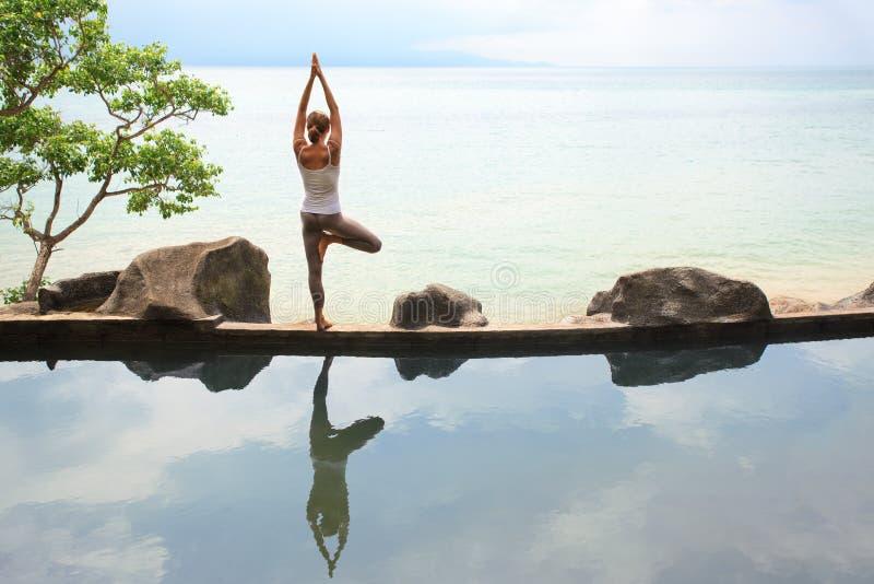 Yoga di pratica di meditazione di mattina della donna alla spiaggia fotografia stock