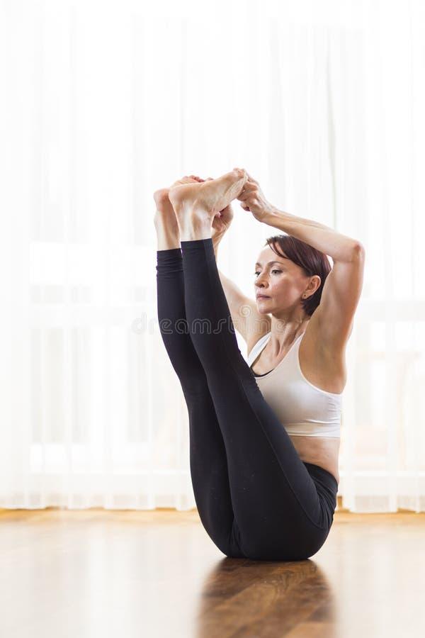 Yoga di pratica e Pilates della donna caucasica di Bunette, facenti esercizio di Paripurna Navasana sulla stuoia del pavimento Se immagine stock