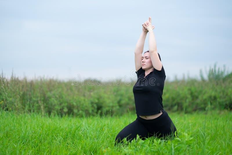 Yoga di pratica o pilates della giovane donna caucasica sul prato o sul campo verde, facente asana diritto fotografia stock libera da diritti