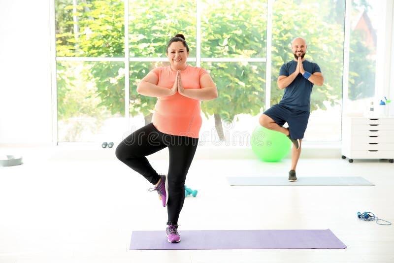 Yoga di pratica di peso eccessivo della donna e dell'uomo fotografia stock libera da diritti