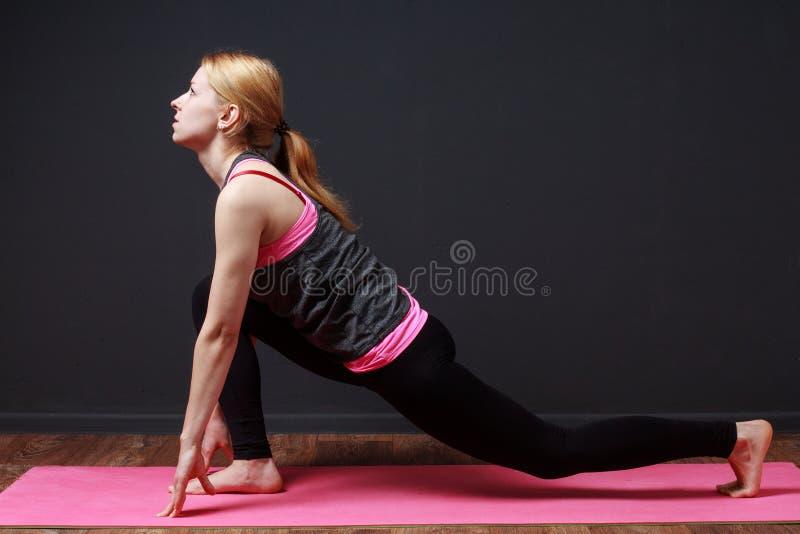 yoga Dianteiro investir contra Mulher loura nova que faz o exercício da ioga imagens de stock royalty free