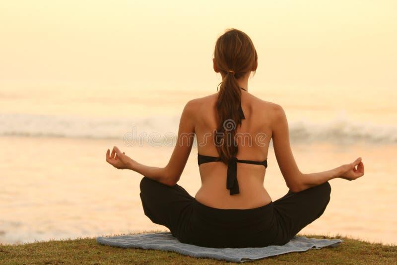 Yoga durch Sonnenuntergang lizenzfreies stockbild