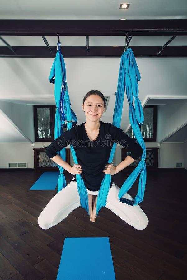 Yoga in einem Reinraum Frau führt Fliegeyoga der körperlichen Bewegungen, pilates auf einer speziellen Ausrüstung durch lizenzfreie stockfotos