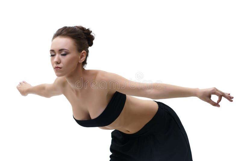 Mujer joven que hace ejercicios de yoga en el fondo de la