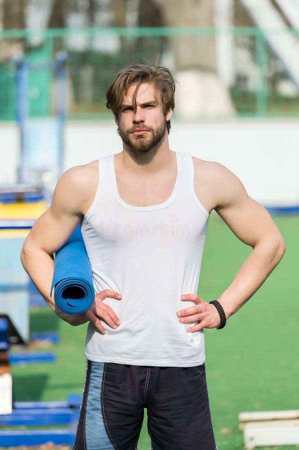 Yoga eller kondition för muskulös man som hållande är matta för övning arkivbilder