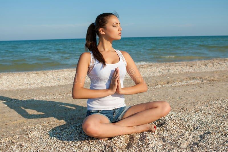 Yoga eller kondition för ung kvinna praktiserande på kusten arkivfoton