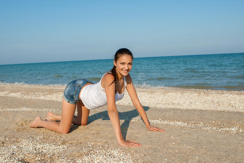 Yoga eller kondition för ung kvinna praktiserande på kusten fotografering för bildbyråer