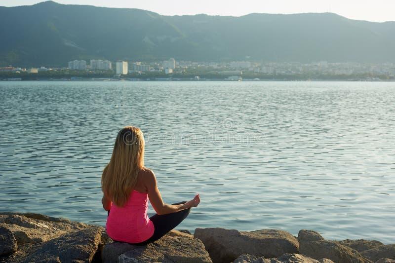 Yoga en el amanecer por el mar, en piedras grandes La muchacha con el pelo rubio largo, adelgaza estructura Relájese y meditación fotos de archivo