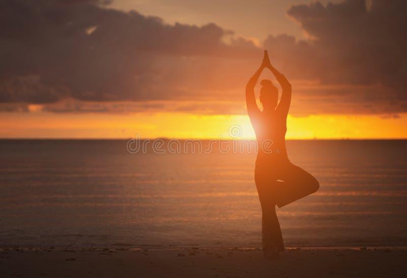 Yoga en el estilo de la silueta de la playa fotografía de archivo libre de regalías