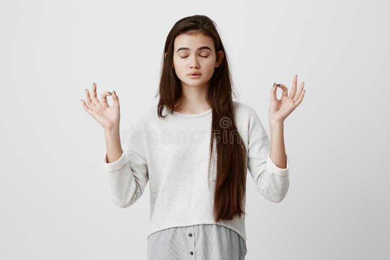 Yoga en meditatie Het mooie terloops geklede donkerbruine meisje die ogen houden sloot terwijl het mediteren, ontspannen voelen royalty-vrije stock foto