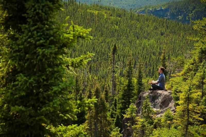 Hombre joven en una roca en el medio de la naturaleza fotografía de archivo